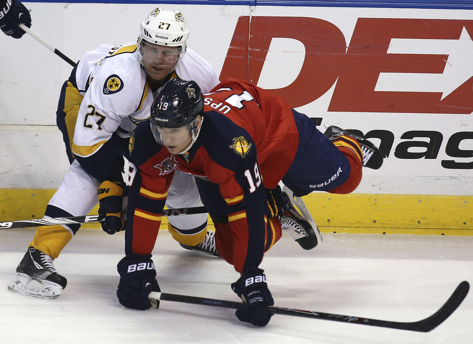 Photo - Nashville Predators' Patric Hornqvist (27) upends Florida Panthers' Scottie Upshall (19) during the first period of a NHL hockey game in Sunrise, Fla., Saturday, Jan. 4, 2014. (AP Photo/J Pat Carter)