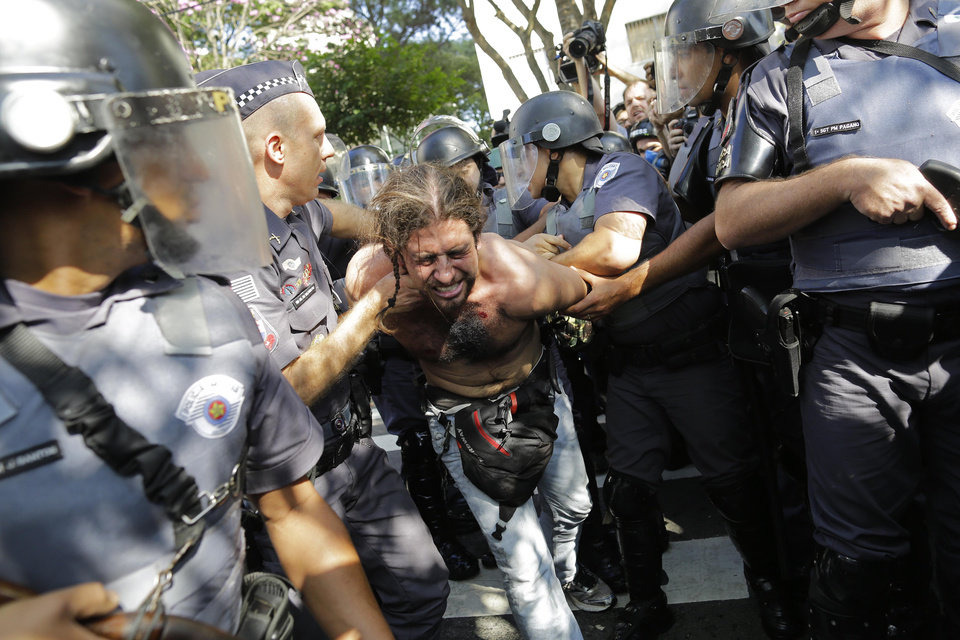 Photo - In this Thursday, June 12, 2014 photo, a protester is detained by police during a demonstration by people demanding better public services and against the money spent on the World Cup soccer tournament in Sao Paulo, Brazil. Police clashed with anti-World Cup protesters trying to block part of the main highway leading to the stadium that hosts the opening match of the tournament. (AP Photo/Nelson Antoine)