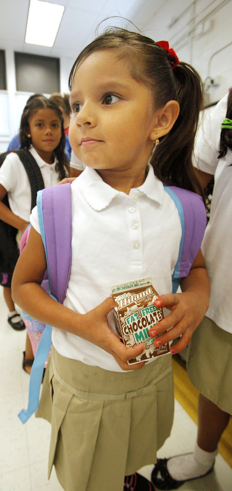 Photo - Kindergarten student Jenniver Martinez, age 5, holding her milk while going through the breakfast line before classes start for the day at Adams Elementary in Oklahoma City Wednesday, Aug. 1, 2012. Wednesday was the first day of classes in the Oklahoma City Public School District.  Photo by Paul B. Southerland, The Oklahoman
