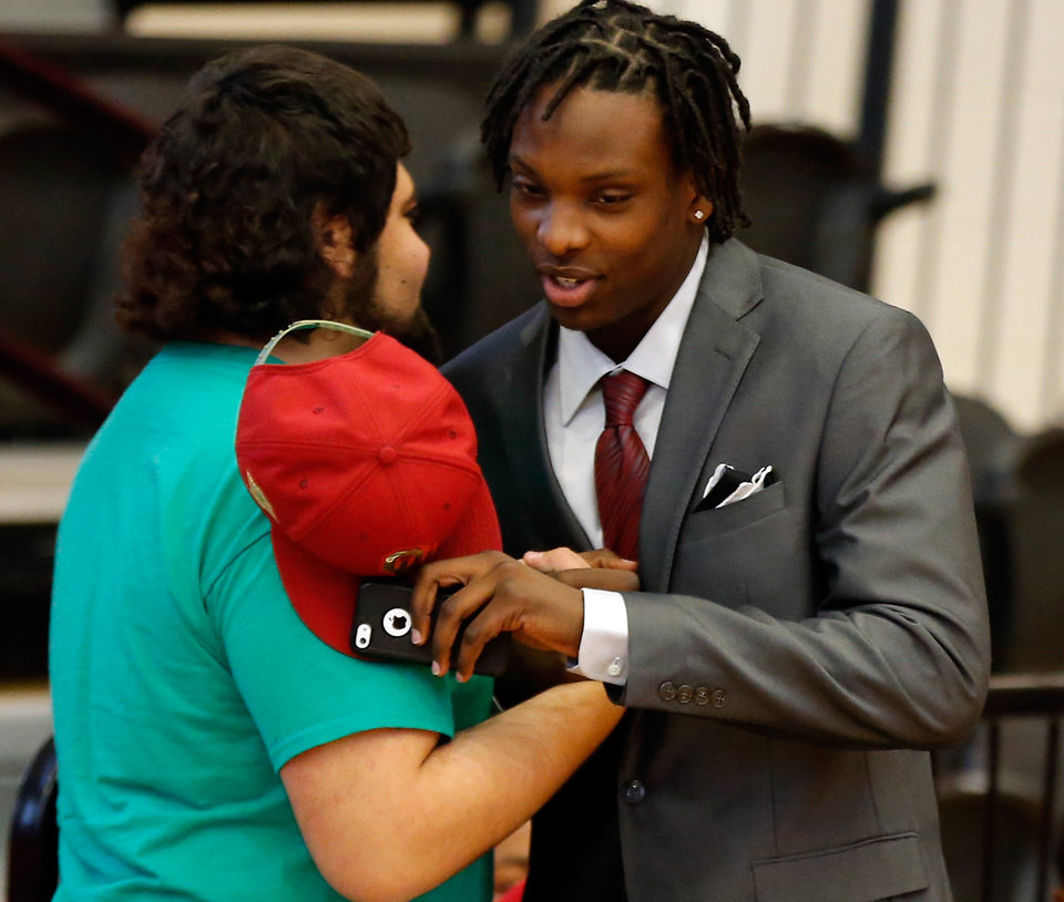 Photo - Dahu Green and teammate Rhett Hall hug as they prepare to sign letters on intent at Westmoore High School on Wednesday, Feb. 4, 2015  in Moore, Okla. Green will attend the University of Oklahoma and Hall will be at Oklahoma Baptist University. Photo by Steve Sisney, The Oklahoman
