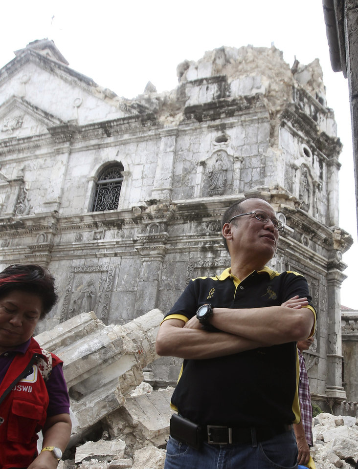 Photo - In this photo released by the Malacanang Photo Bureau, Philippine President Benigno Aquino III, right, stands beside the damaged Basilica Del Santo Nino in quake-hit Cebu, central Philippines on Wednesday Oct. 16, 2013. The 7.2-magnitude earthquake that struck the central Philippines and killed more than a hundred people also dealt a serious blow to the region's historical and religious legacy by heavily damaging a dozen or more churches, some of them hundreds of years old. (AP Photo/ Ryan Lim, Malacanang Photo Bureau)