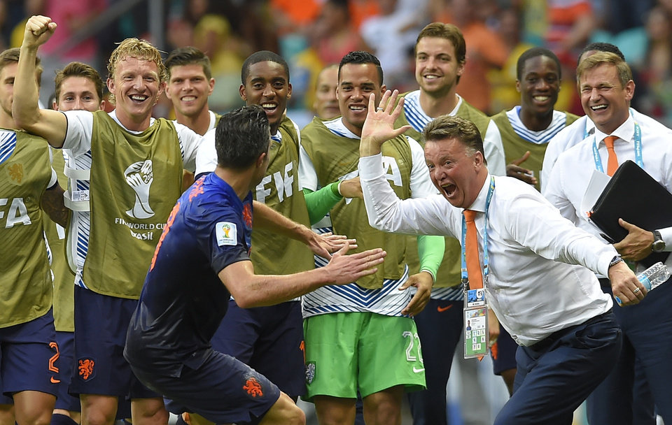 Photo - Netherlands' Robin van Persie celebrates with Netherlands' head coach Louis van Gaal after scoring a goal during the group B World Cup soccer match between Spain and the Netherlands at the Arena Ponte Nova in Salvador, Brazil, Friday, June 13, 2014. (AP Photo/Manu Fernandez)