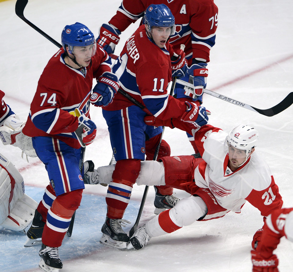 Photo - Detroit Red Wings left wing Tomas Tatar (21) is checked by Montreal Canadiens right wing Brendan Gallagher (11) as Canadiens defenseman Alexei Emelin (74) looks up the ice during the second period of an NHL hockey game Wednesday, Feb. 26, 2014, in Montreal. (AP Photo/The Canadian Press, Ryan Remiorz)