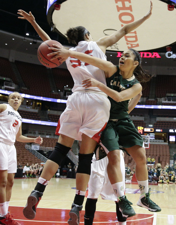 Photo - Cal Poly's Ariana Elegado, right, passes the ball behind Cal State Northridge's Jasmine Johnson during the first half of an NCAA college basketball game in the final of the Big West Conference tournament, on Saturday, March 15, 2014, in Anaheim, Calif. (AP Photo/Jae C. Hong)
