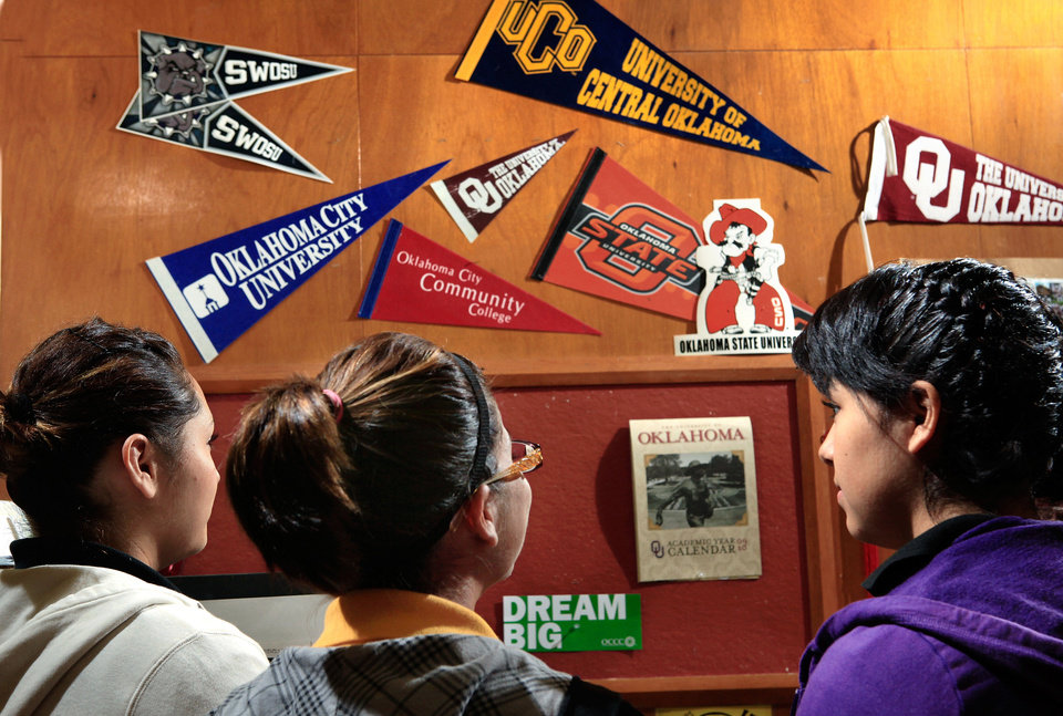 Photo - Undocumented students at Santa Fe South High School in Oklahoma City stand in front of a wall with university pennants in 2010. One of the students pictured is now attending a state university and hopes to qualify for relief under extended prosecutorial discretion announced by President Barack Obama on June 15.  JIM BECKEL - THE OKLAHOMAN