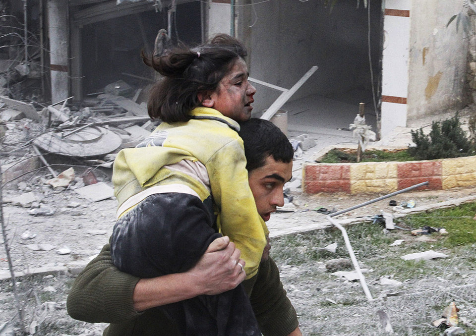 Syrian man carries his sister who was wounded in a government airstrike hit the neighborhood of Ansari, in Aleppo, Syria, Sunday, Feb. 3, 2013. The Britain-based activist group Syrian Observatory for Human Rights, which opposes the regime, said government troops bombarded a building in Aleppo\'s rebel-held neighborhood of Eastern Ansari that killed over 10 people, including at least five children. (AP Photo/Abdullah al-Yassin)