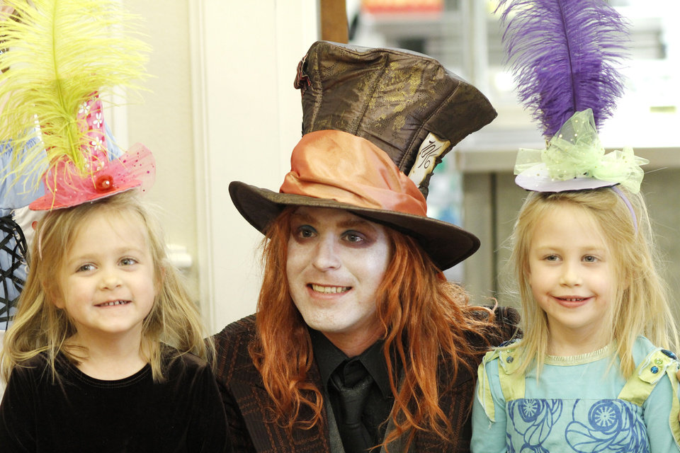 Photo - 5 year old twins Hannah Snyder, left, and Olivia Snyder, right, pose with the Mad Hatter played by Matthew White, at the Daddy-Daughter Mad Hatter Tea Party at the Edmond Multi-purpose Community Center Sunday, Feb. 12, 2012. Photo by Doug Hoke, The Oklahoman ORG XMIT: OKC1202091803570754
