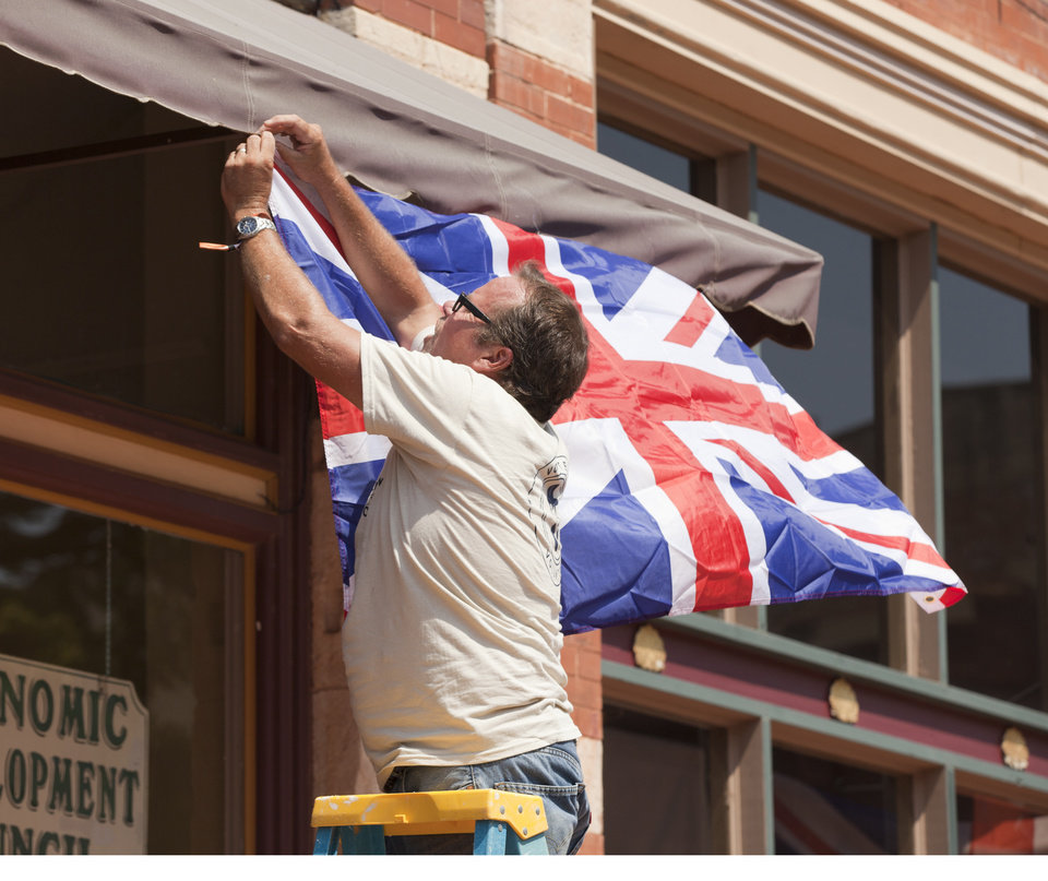Photo - Gentlemen of the Road Stopover volunteer Brian Bothroyd hangs a Union Jack flag in downtown Guthrie on Friday, September 6, 2013. Photo by Nathan Poppe, for The Oklahoman