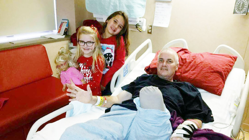 Photo - Hadley Wyatt (left) and her sister, Mia, both of Chattanooga, Ok., visit with Leo Schmitz in his Tulsa hospital room in December, 2016. The Wyatt family credits Schmitz with preventing their daughter from serious injury when a car plowed into a crowd at the Oct. 24, 2016 OSU homecoming parade. Schmitz suffered severe injuries that required the amputation of  his leg.