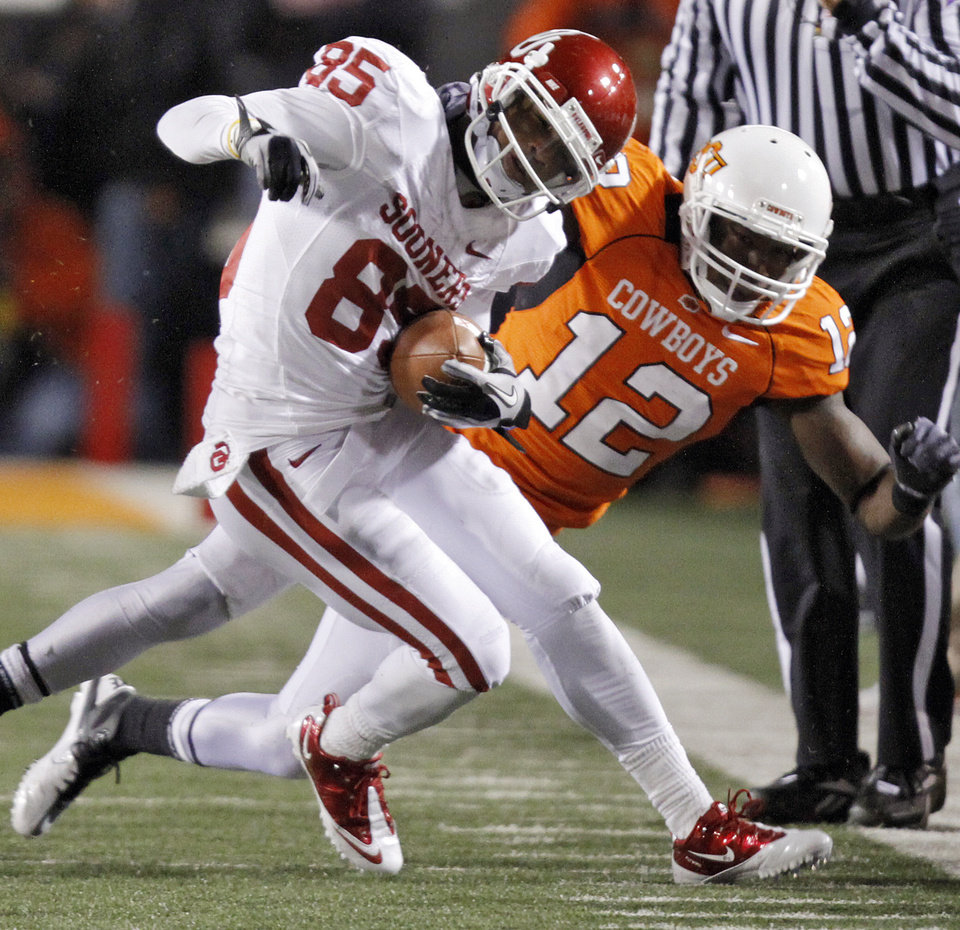 Photo - Oklahoma's Ryan Broyles (85) is brought down by Oklahoma State's Johnny Thomas (12) during the Bedlam college football game between the University of Oklahoma Sooners (OU) and the Oklahoma State University Cowboys (OSU) at Boone Pickens Stadium in Stillwater, Okla., Saturday, Nov. 27, 2010. Photo by Chris Landsberger, The Oklahoman