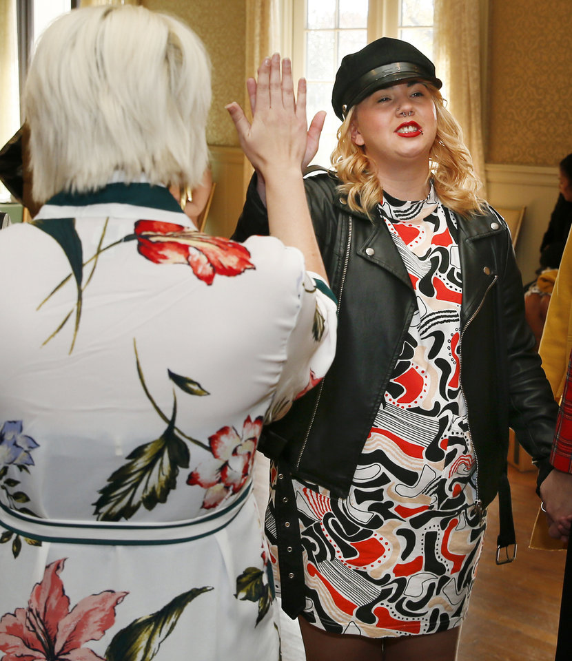 Photo -  Montana Church, at right, high fives Lynde Gleason, with TEEM, before walking the runway at the