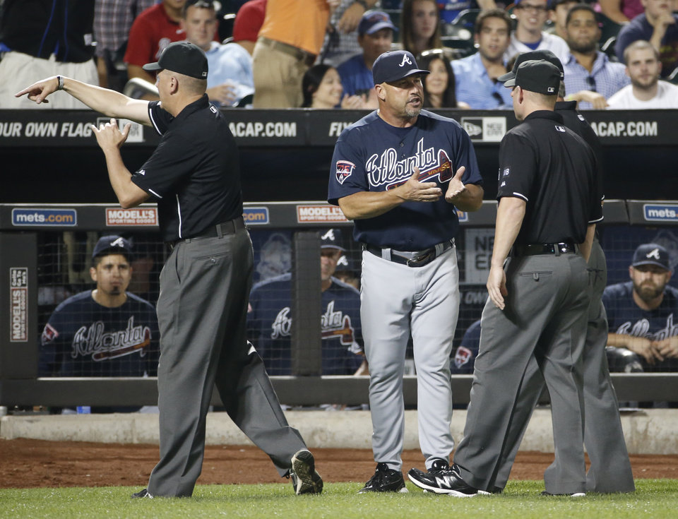 Photo - Third base umpire Mike Everitt (57), the crew chief, tosses Atlanta Braves manager Fredi Gonzalez from the game as Gonzalez  argues the call on a second base play in a tie-game in the ninth inning of a baseball game against the New York Mets in New York, Monday, July 7, 2014. (AP Photo/Kathy Willens)