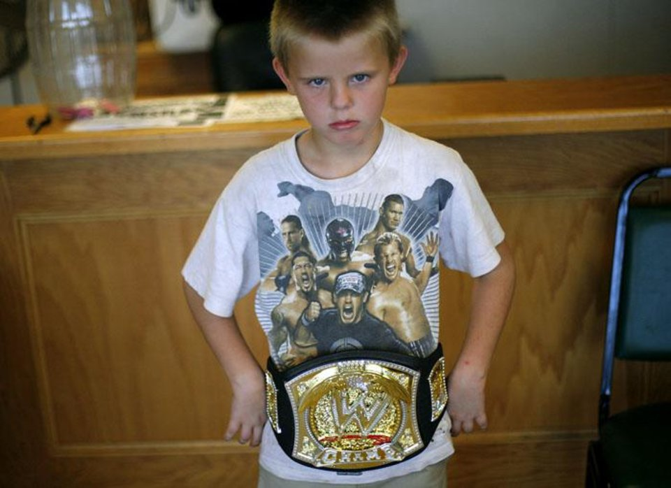 Photo -  Zack Whitaker, age 8, poses with his toy championship belt prior to an event at the Golden Goose Flea Market Event Center in Midwest City on Sunday, Aug. 23, 2009.  Whitaker says his dream is to be a wrestler. By John Clanton, The Oklahoman