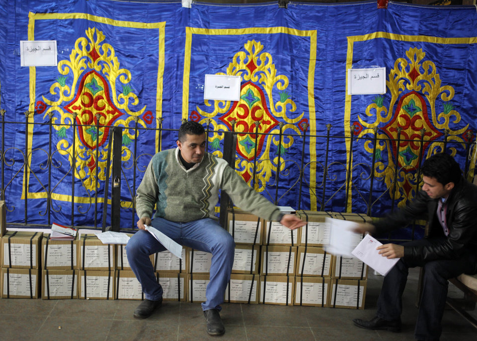 Photo - An Egyptian worker sits on boxes of ballots while receiving a list of polling stations from a colleague, at the Giza courthouse, in Cairo, Egypt, Monday, Jan. 13, 2014. The January 14-15 vote on the draft constitution will be the first real test of the post-Morsi regime. A comfortable
