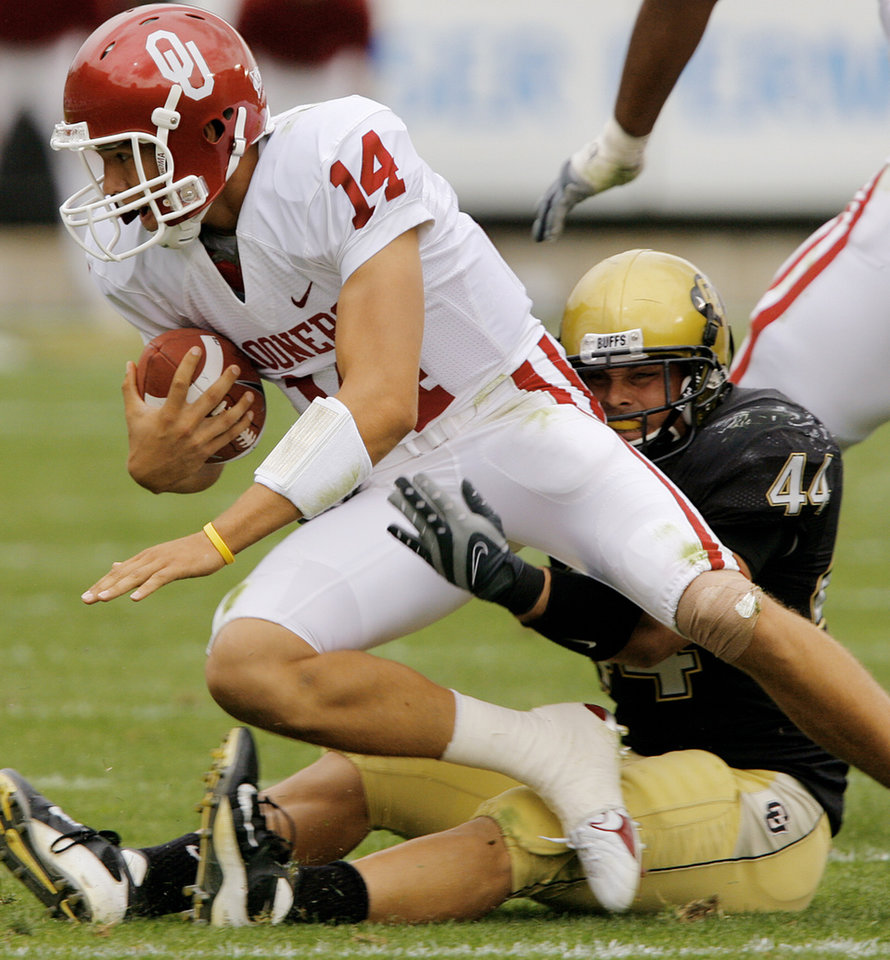 Oklahoma quarterback Sam Bradford (14) is sacked by Colorado\'s Jordon Dizon (44) during the second half of the college football game between the University of Oklahoma Sooners (OU) and the University of Colorado Buffaloes (CU) at Folsom Field on Saturday, Sept. 28, 2007, in Boulder, Co. By CHRIS LANDSBERGER, The Oklahoman