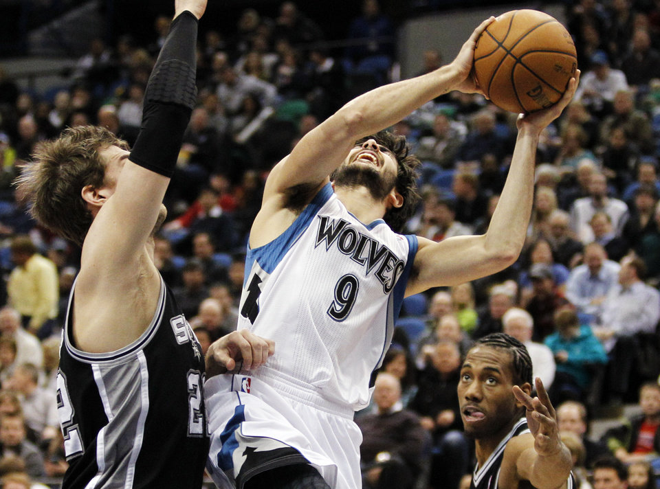 Minnesota Timberwolves guard Ricky Rubio (9), of Spain, drives between San Antonio Spurs center Tiago Splitter, left, of Brazil, and forward Kawhi Leonard, right, during the second half of an NBA basketball game Wednesday, Feb. 6, 2013 in Minneapolis. The Spurs won 104-94. (AP Photo/Genevieve Ross)