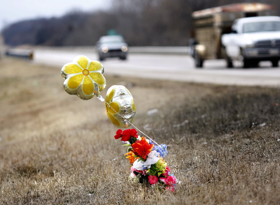 Photo - Flowers and a balloon bouquet mark the spot on SH 377 Monay, March 11, 2019, where three people died in a crash last week. Konawa Middle School athlete Rhindi Kay Isaacs, 12, was among three people who died in a fiery, head-on collision Friday evening. The Konawa Public School District said six students from the  junior high school girls softball team were aboard the bus  traveling home at the time of the crash. The team's coach was driving the bus when it was struck by an SUV on SH 377, between Bowlegs and Konawa, in Seminole County. The Oklahoma Highway Patrol said the SUV was traveling in the northbound lane just after 7 p.m. when it swerved and collided with a Konawa School activity bus after the driver of the SUV swerved when passing another vehicle, 