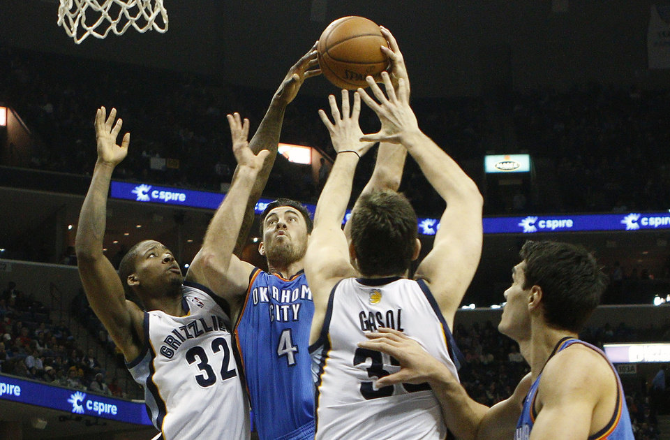 Photo - Oklahoma City Thunder forward Nick Collison (4) goes to the basket against Memphis Grizzlies forward Ed Davis (32) and center Marc Gasol (33), of Spain, in the first half of an NBA basketball game, Tuesday, Jan. 14, 2014, in Memphis, Tenn. (AP Photo/Lance Murphey)