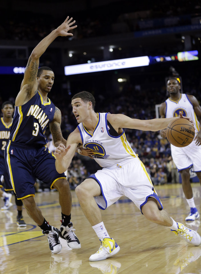 Photo - Golden State Warriors' Klay Thompson (11) tries to dribble around Indiana Pacers' George Hill (3) during the first half of an NBA basketball game in Oakland, Calif., Saturday, Dec. 1, 2012. (AP Photo/Marcio Jose Sanchez)