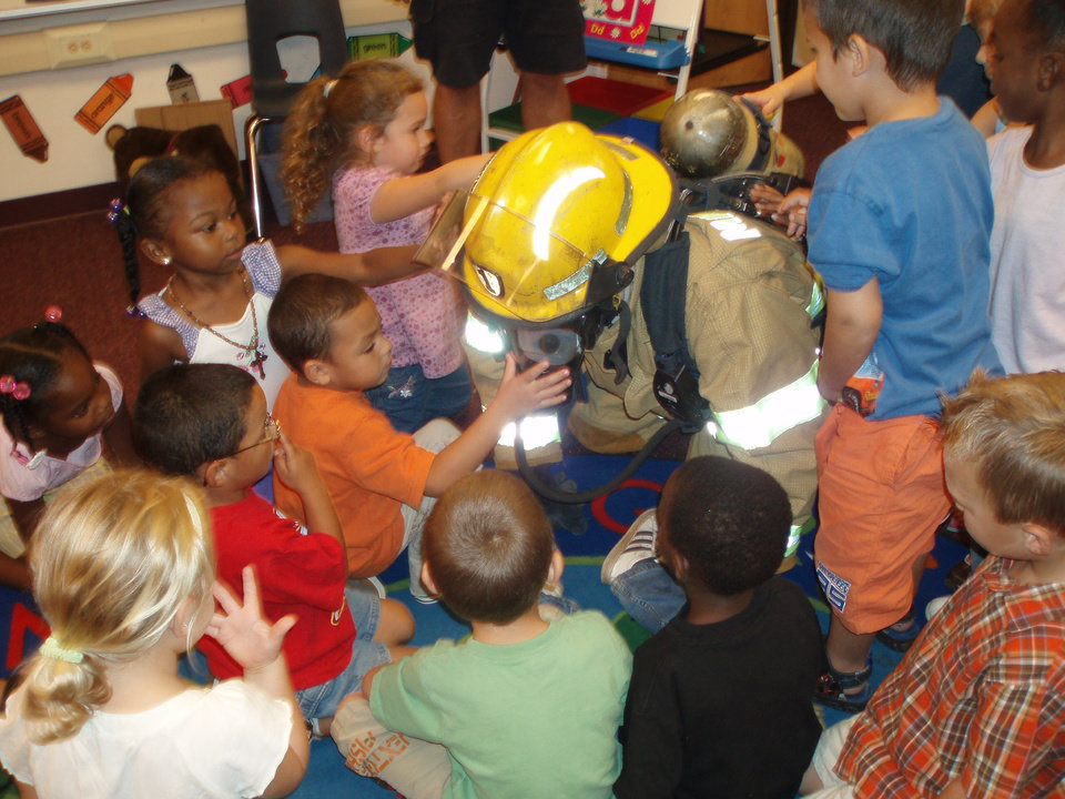 Midwest City firefighter, Todd Cantrell, letting local elementary school students touch his  firefighting uniform and mask.  This is done to help young children recognize what a firefighter looks like during a fire.<br/><b>Community Photo By:</b> Casey Rooney<br/><b>Submitted By:</b> Casey, Oklahoma city