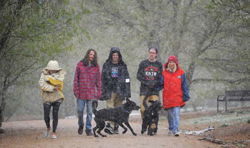 Photo - Left to right, Cassandra Cantu, Daniel Thorp, Aaron Smith, Jarred Smith and Jes Unruh walk their dogs in the Bear Creek Dog Park in Colorado Springs, Colo. as snow begins to fall Sunday afternoon, May 11, 2014. (AP Photo/The Gazette, Mark Reis)