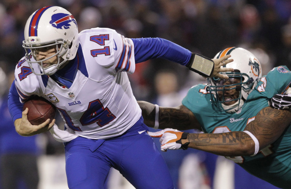 Photo -   Buffalo Bills quarterback Ryan Fitzpatrick (14) breaks a tackle by Miami Dolphins defensive tackle Randy Starks (94) during the second half of an NFL football game on Thursday, Nov. 15, 2012, in Orchard Park, N.Y. (AP Photo/Bill Wippert)