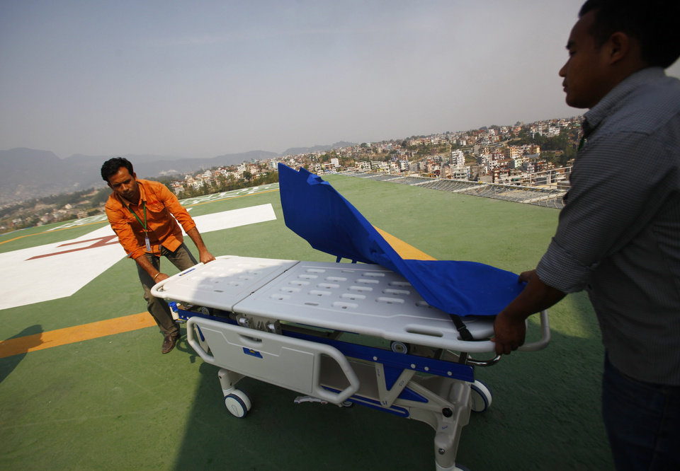 Photo - Hospital staff get ready to receive the injured from an avalanche, on helipad of Grandy hospital, in Katmandu, Nepal, Friday, April 18, 2014. An avalanche swept down a climbing route on Mount Everest early Friday, killing at least 12 Nepalese guides and leaving three missing in the deadliest disaster on the world's highest peak. (AP Photo/Niranjan Shrestha)