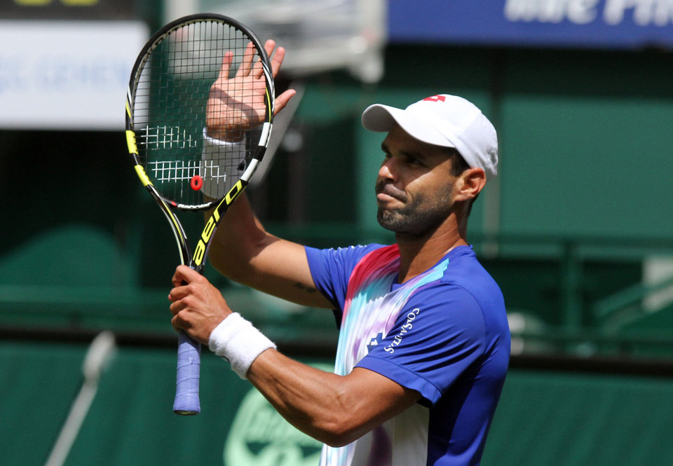 Photo - Colombia's Alejandro Falla celebrates winning against Germany's Peter Gojowczyk during the quarterfinal match at the Gerry Weber Open tennis tournament in Halle, Germany, Friday, June 13, 2014. Falla won the match with 7-6 and 7-6. (AP Photo/dpa, Oliver Krato)