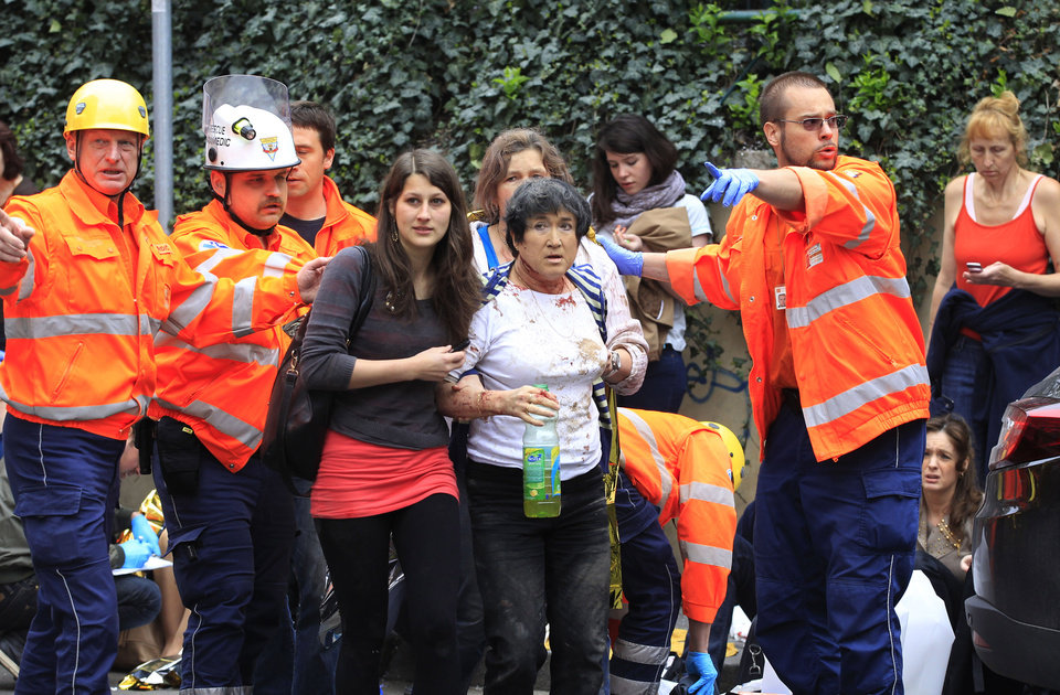 Photo - Paramedics help injured people after an explosion in downtown Prague, Czech Republic, Monday, April 29, 2013.  Police said a powerful explosion has damaged a building in the center of the Czech capital and they believe some people are buried in the rubble. (AP Photo/Petr David Josek)