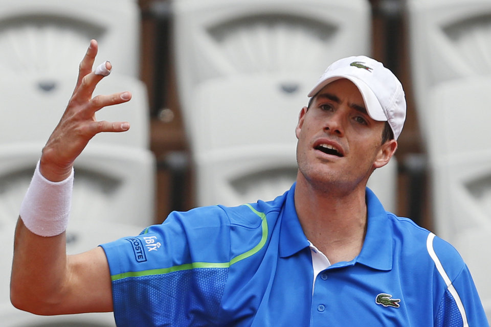 Photo - John Isner of the U.S. misses a return during the fourth round match of the French Open tennis tournament against Tomas Berdych of the Czech Republic at the Roland Garros stadium, in Paris, France, Sunday, June 1, 2014. Berdych won in three sets 6-4, 6-4, 6-4. (AP Photo/Darko Vojinovic)