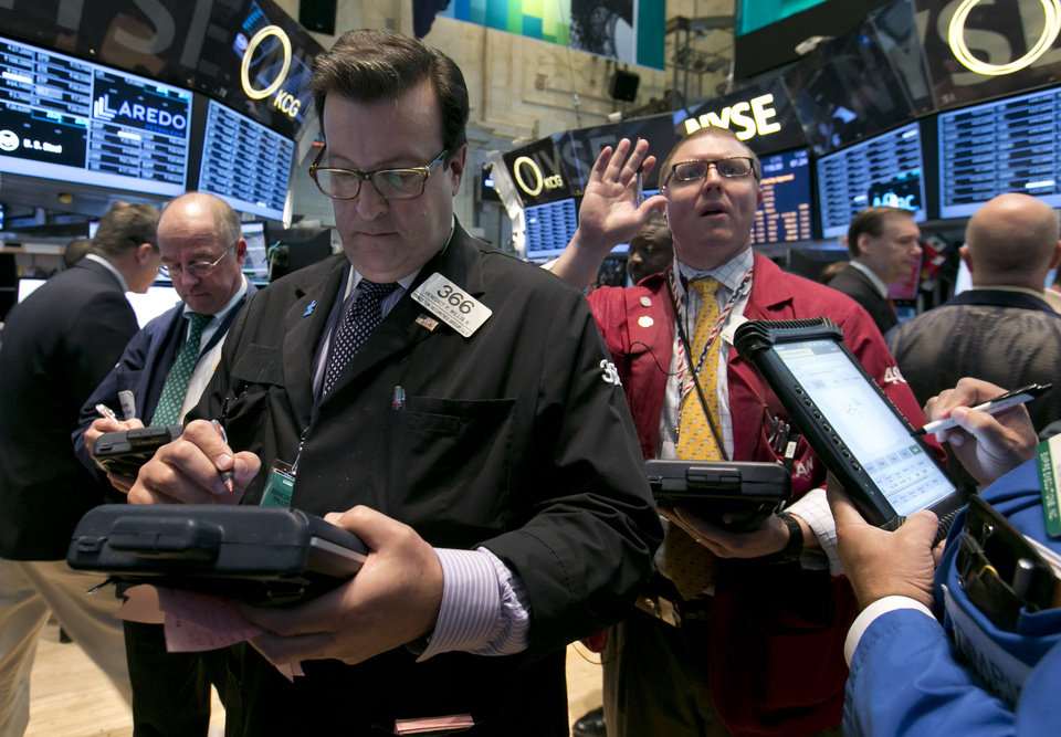 Photo - Trader Benedict Willis, foreground left, works on the floor of the New York Stock Exchange, Tuesday, April 22, 2014. Stock futures edged higher as more companies reported first quarter earnings. (AP Photo/Richard Drew)