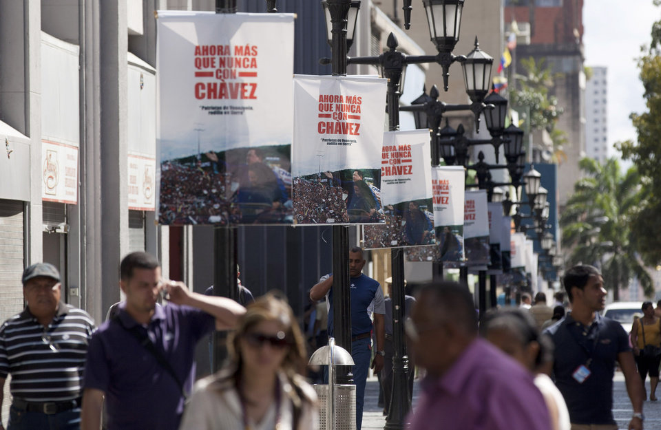 "Pedestrians walk on a street lined with posters that show an image of Venezuela's President Hugo Chavez and read in Spanish: ""Now more than ever with Chavez,"" in Caracas, Venezuela, Friday, Jan. 4, 2013. Chavez hasn't spoken publicly or been seen since his Dec. 11 operation in Cuba, and the latest report from his government Thursday night increased speculation that he is unlikely to attend his Jan. 10 inaugural ceremony. (AP Photo/Ariana Cubillos)"