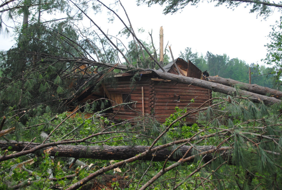Photo - The historic log cabin at Northside Park in Philadelphia, Miss. is destroyed by fallen trees after a storm Wednesday, April 27, 2011. A wave of thunderstorms with winds blowing near hurricane force strafed the South on Wednesday, killing at least 15 people from Arkansas to Alabama. (AP Photo/The Neshoba Democrat, Steven Thomas)