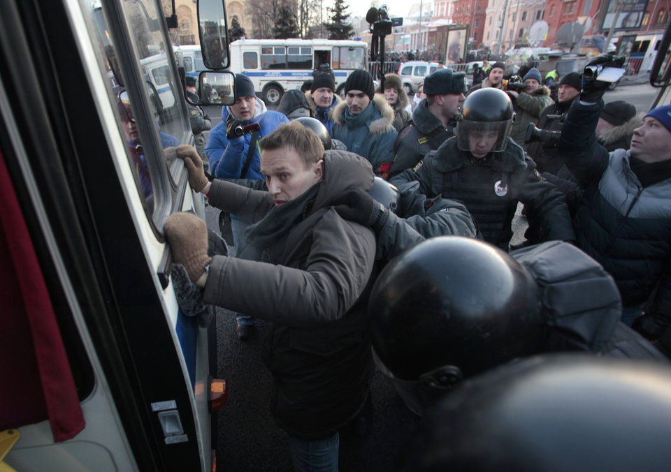 Police officers detain opposition leader Alexei Navalny during an unauthorized rally in Lubyanka Square in Moscow, Saturday, Dec. 15, 2012. Thousands of opposition supporters have gathered in central Moscow for an unauthorized rally where several prominent opposition figures have been detained.(AP Photo/Pavel Golovkin)