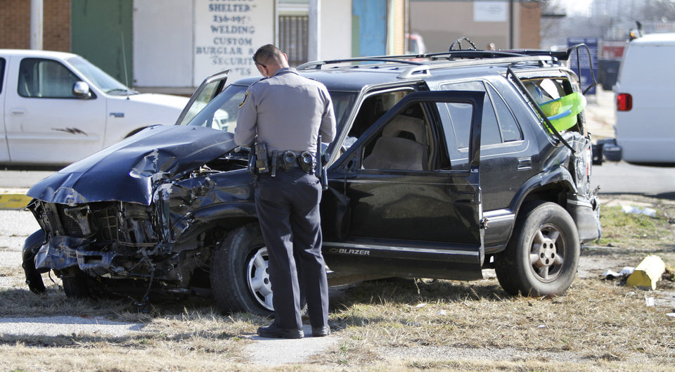An Oklahoma City police officer examines a sport utility vehicle after it was hit by a Metro Transit bus at Linwood Avenue and N Indiana Avenue in Oklahoma City, Thursday, February  16,  2012. Twelve people were taken by ambulance to area hospitals. Photo By Steve Gooch, The Oklahoman