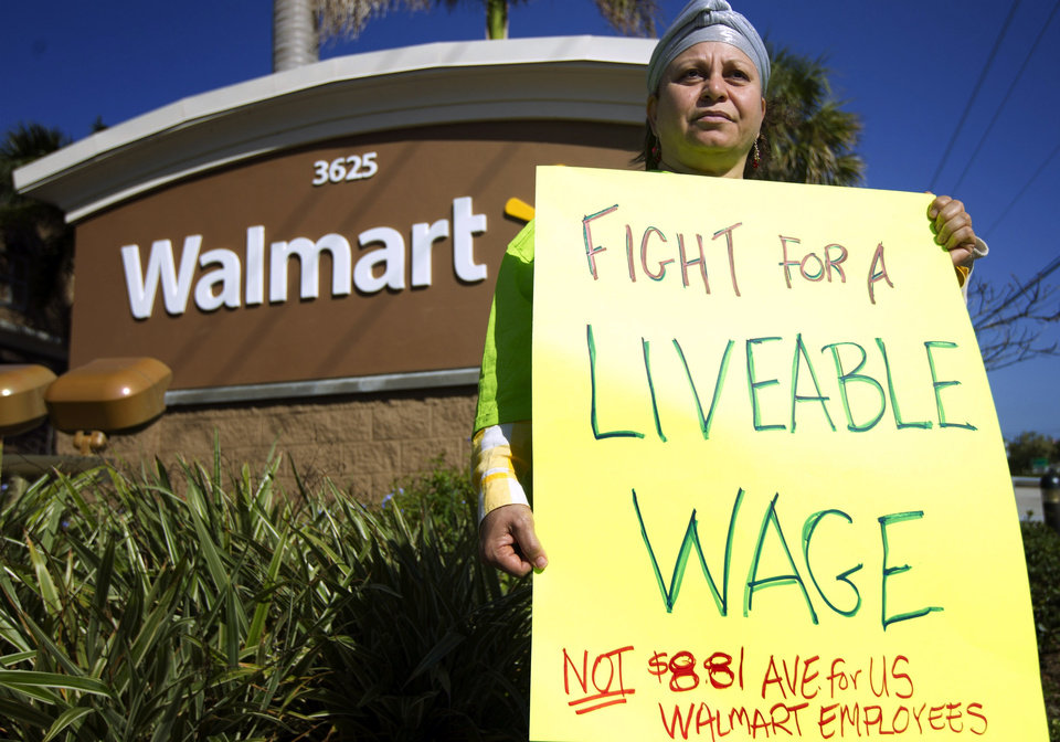 Photo -   Nawal Elmilliax joins the protest against Wal-Mart in Boynton Beach, Fla., Friday, Nov 23, 2012. Wal-Mart employees and union supporters are taking part in today's nationwide demonstration for better pay and benefits A union-backed group called OUR Walmart, which includes former and current workers, was staging the demonstrations and walkouts at hundreds of stores on Black Friday, the day when retailers traditionally turn a profit for the year. (AP Photo/J Pat Carter)