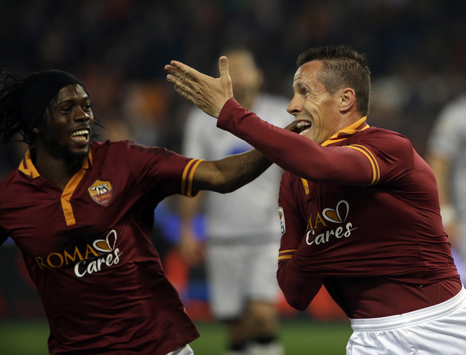 Photo - Roma's Rodrigo Taddei, right, celebrates with teammate Gervinho after scoring during a Serie A soccer match between Roma and Atalanta in Rome's Olympic stadium, Saturday, April 12, 2014. (AP Photo/Gregorio Borgia)