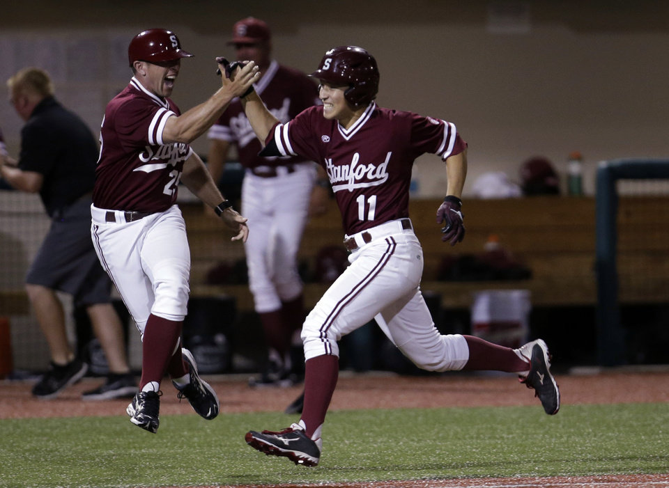 Photo - Stanford's Tommy Edman (11) gets a high five from assistant coach Brock Ungricht (25) after hitting the game winning home run against Indiana during an NCAA college baseball regional tournament game in Bloomington, Ind.,  Monday, June 2, 2014. Stanford won the rain delayed game 5-4. (AP Photo/AJ Mast)
