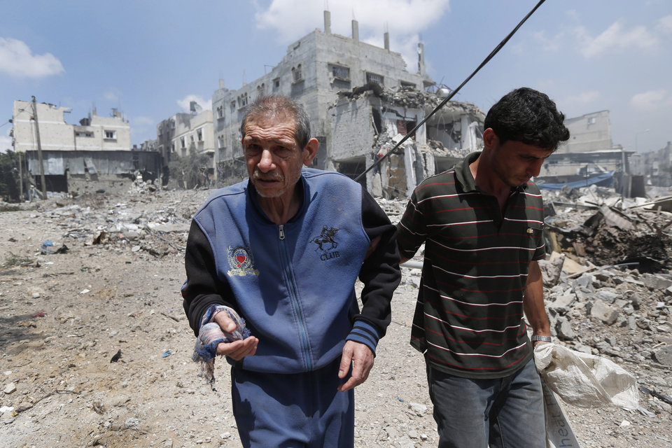 Photo - FILE - In this Sunday, July 20, 2014, file photo, a Palestinian man is helped to flee Gaza City's Shijaiyah neighborhood, after an Israeli strike in the area. Disagreement over whether to lift the Gaza blockade is a key stumbling block to ending more than two weeks of fighting between the Islamic militant Hamas and Israel. Some in Gaza say they would rather endure more fighting than return to life under the blockade. (AP Photo/Lefteris Pitarakis, File)