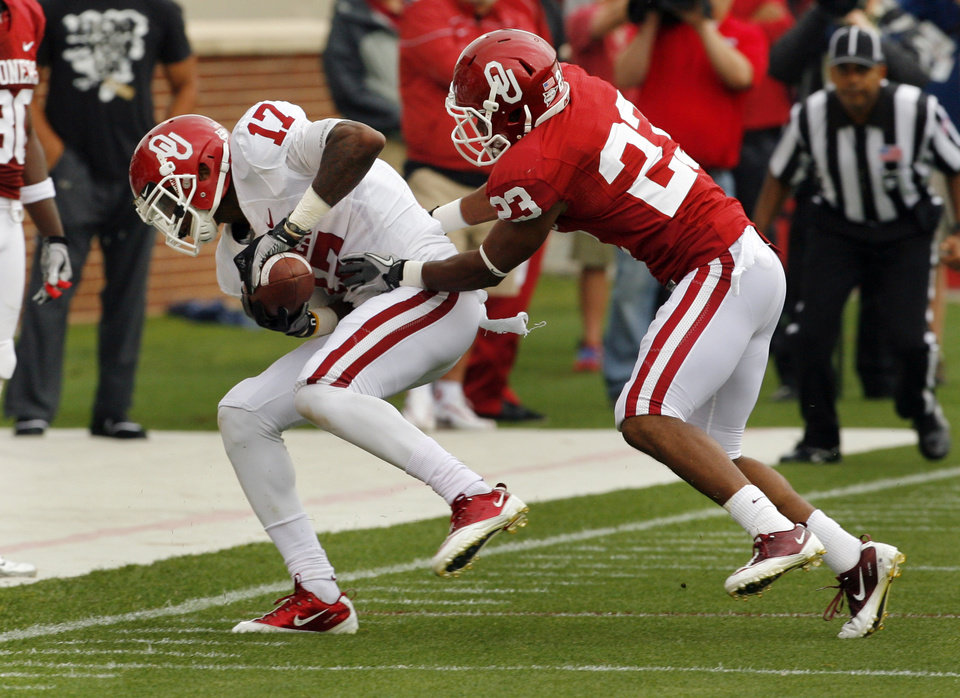 Photo - Trey Metoyer (17) is pushed out of bounds after a catch by Kass Everett (23) during the University of Oklahoma (OU) football team's annual Red and White Game at Gaylord Family/Oklahoma Memorial Stadium on Saturday, April 14, 2012, in Norman, Okla.  Photo by Steve Sisney, The Oklahoman