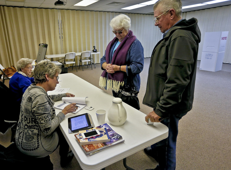 Volunteer Cindy Ward checks in Barbara and Carlos Fox to vote at the First Baptist Church on Tuesday Jan. 8, 2013, in El Reno, Okla. for a school bond issue that could lead to the purchase of land and demolition of the church. The new acquisition would be used to build a new math and science wing for the high school. The church is in the process of relocating closer to I-40 in El Reno.  Photo by Chris Landsberger, The Oklahoman