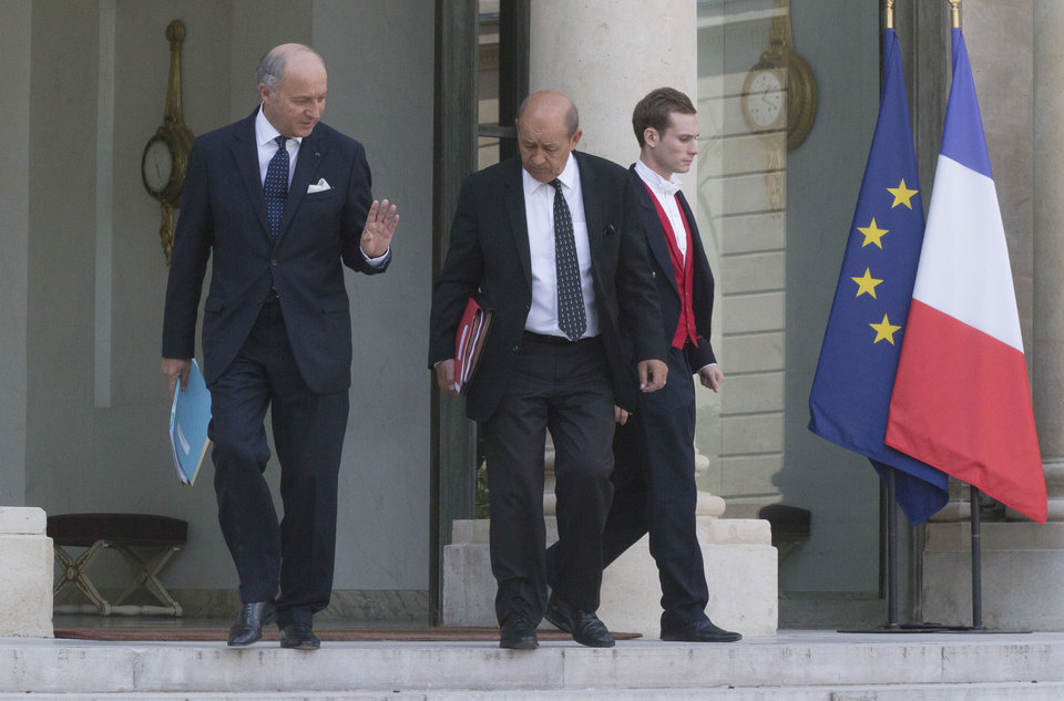 Photo - French Foreign Minister Laurent Fabius, left, and  French defense minister Jean-Yves Le Drian, leave the Elysee Palace after a defense meeting in Paris, Wednesday Aug. 28, 2013. French President Francois Hollande said Tuesday, that France was prepared to take action against those responsible for gassing people in Syria.(AP Photo/Michel Euler)