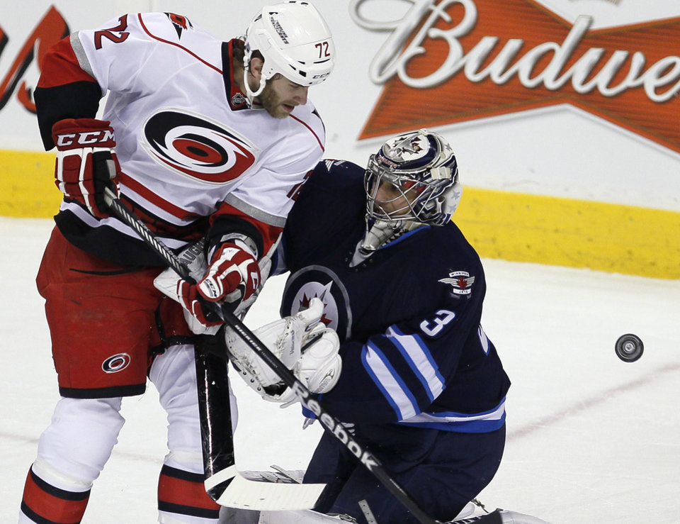 Photo - Carolina Hurricanes' Nicolas Blanchard (72) cannot knock a loose puck past Winnipeg Jets goaltender Ondrej Pavelec (31) during the first period of their NHL hockey game in Winnipeg, Manitoba, Thursday, April 18, 2013. (AP Photo/The Canadian Press, John Woods)