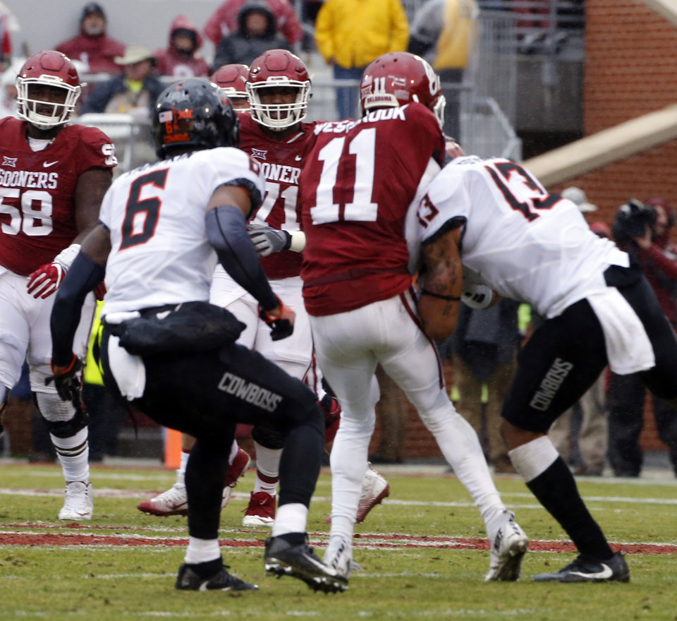 Photo - Oklahoma's Dede Westbrook (11) is hurt on a hit by Oklahoma State's Jordan Sterns (13) during the Bedlam college football game between the Oklahoma Sooners (OU) and the Oklahoma State Cowboys (OSU) at Gaylord Family - Oklahoma Memorial Stadium in Norman, Okla., Saturday, Dec. 3, 2016. Photo by Steve Sisney, The Oklahoman