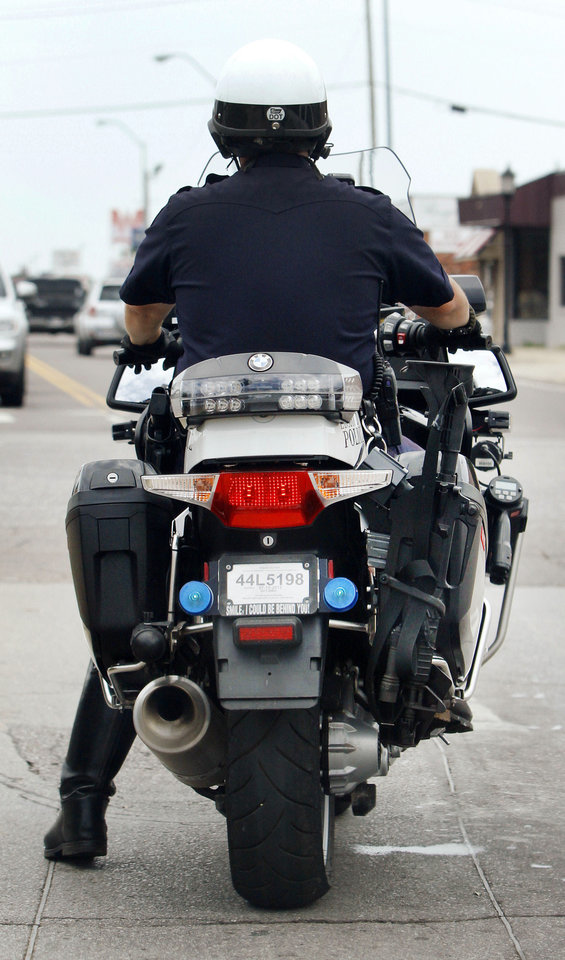 Photo - An Edmond police officer rides one of the departments new BMW motorcycles equipped with an AR-15 assault rifle in Edmond, Thursday July 11, 2013. Photo By Steve Gooch, The Oklahoman