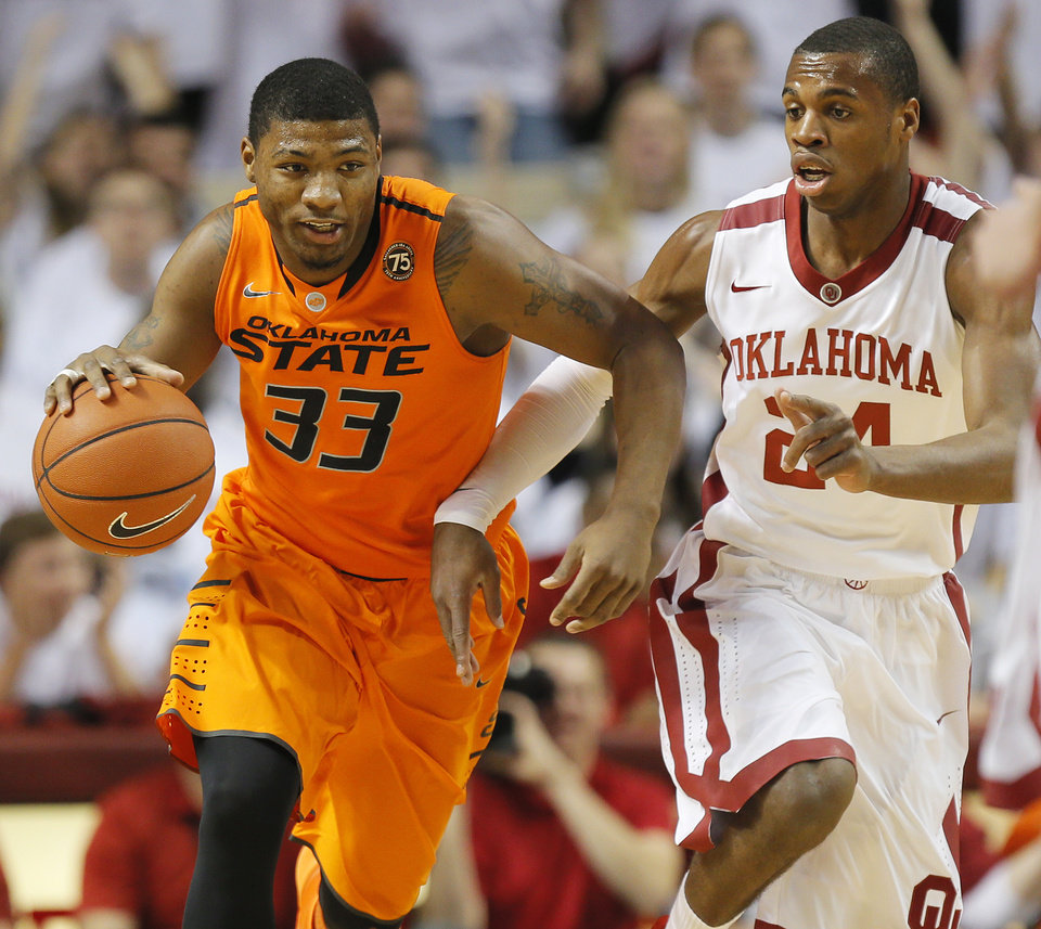 Oklahoma State's Marcus Smart (33) drives the ball past Oklahoma's Buddy Hield (24) in the first half during the NCAA men's Bedlam basketball game between the Oklahoma State Cowboys (OSU) and the Oklahoma Sooners (OU) at Lloyd Noble Center in Norman, Okla., Monday, Jan. 27, 2014. Photo by Nate Billings, The Oklahoman