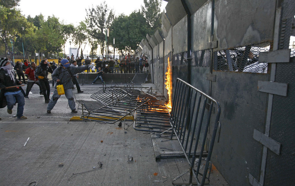 Protestors clash with police outside the steel security barriers around the National Congress, where the swearing in of new Mexican President Enrique Pena Nieto will take place in Mexico City, Sunday, Dec. 1, 2012.  Pena Nieto took power at midnight in a symbolic ceremony and will formally take the oath of office Saturday morning after campaigning as the face of a new PRI _ a party that claims to be repentant and reconstructed after voted out of the presidency in 2000.(AP Photo / Marco Ugarte)