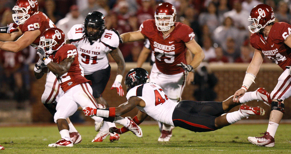 Oklahoma\'s Roy Finch (22) runs past Texas Tech\'s Daniel Cobb (42) during the college football game between the University of Oklahoma Sooners (OU) and the Texas Tech University Red Raiders (TTU) at Gaylord Family-Oklahoma Memorial Stadium in Norman, Okla., Saturday, Oct. 22, 2011. Photo by Bryan Terry, The Oklahoman