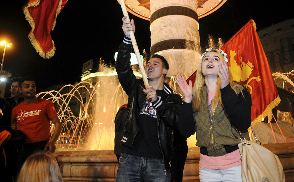 Photo - Supporters of the ruling conservative VMRO-DPMNE wave party flags celebrating the double victory in parliamentary and presidential elections, in downtown Skopje, Macedonia, early Monday, April 28, 2014. Macedonia's incumbent prime minister claimed a landslide victory late Sunday in parliamentary and presidential elections, but the center-left opposition denounced what it called distorting interference in the democratic process by the ruling party and said it won't recognize the results. (AP Photo/Boris Grdanoski)