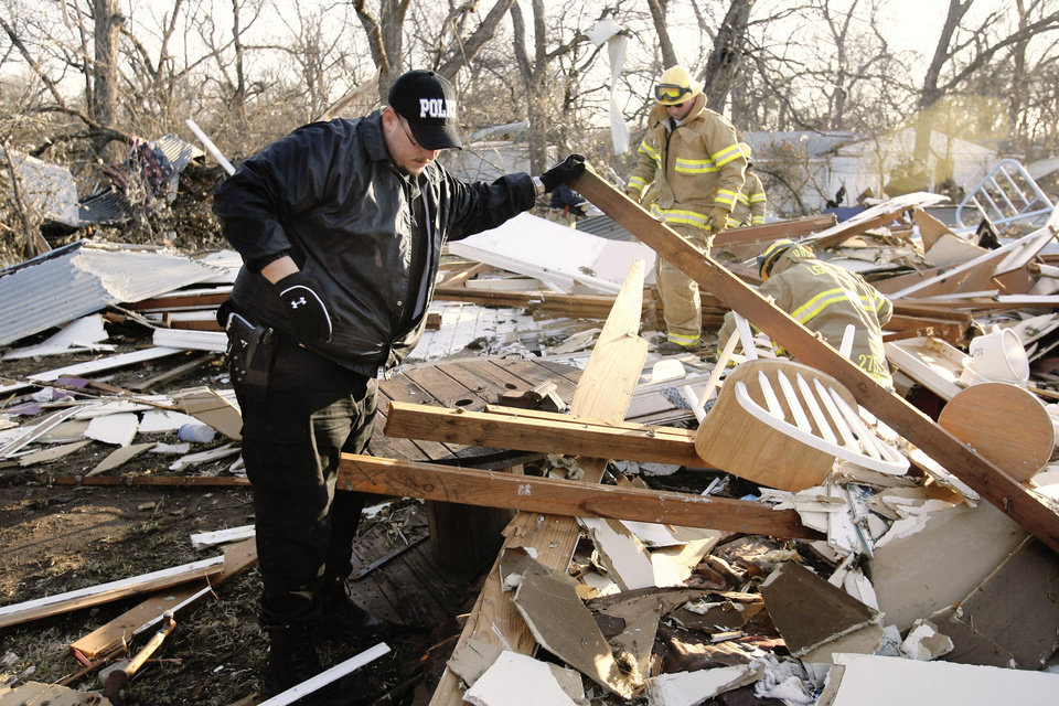 Ringling police officer Wayne Thompson searches a home with the Lone Grove firemen in the background on the north side of SH 70 in Lone Grove, Wednesday, Feb. 11, 2009. BY PAUL B. SOUTHERLAND, THE OKLAHOMAN
